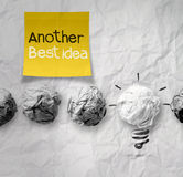 Hand holding sticky note with another idea light bulb on crumple Stock Photography