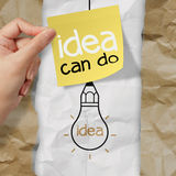 Hand holding sticky note with idea can do word  light bulb on cr. Umpled paper as creative concept Stock Image