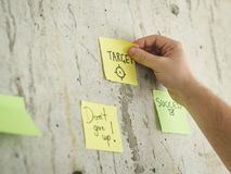 Hand holding sticky note with message target on wall. Hand holding sticky note with message target Stock Images