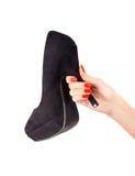 Hand holding a stiletto shoe. Stock Photo