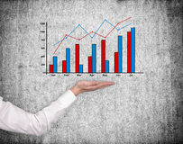 Hand holding stock chart. On gray wall background Stock Photo