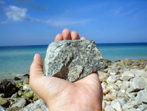 Hand holding a stone. Sea view with hand and stone stock image
