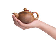 Hand holding stone teapot on white background. Royalty Free Stock Photo