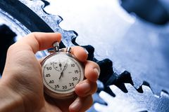 Hand holding stopwatch and cogwheels Royalty Free Stock Photography