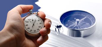 Hand holding stopwatch, paper cards and compass Stock Photos