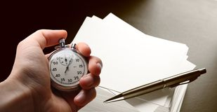 Hand holding stopwatch and pen Stock Photos