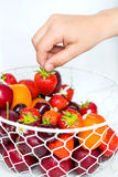 Hand holding Strawberry above Summer Berries and Fruits in the b Stock Photography