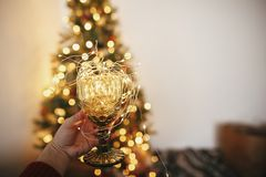 Hand holding stylish vintage glass with garland bulbs inside on stock photo