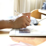Hand holding stylus pen. While working on tablet attached to computer Royalty Free Stock Images
