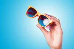 Hand holding sunglasses Royalty Free Stock Photos