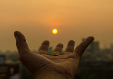 Hand holding sunset and city of background Royalty Free Stock Photos