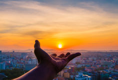 Hand holding sunset and city of background royalty free stock photo