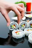 Hand holding sushi on black background Stock Images