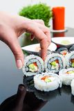 Hand holding sushi on black background Royalty Free Stock Image