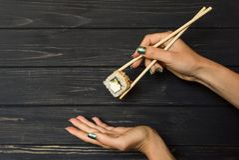 Hand holding sushi with chopsticks Stock Image