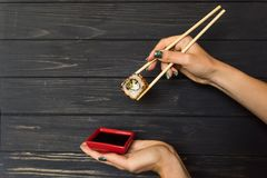 Hand holding sushi with chopsticks on a black wooden background Stock Photos