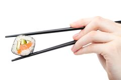 Hand holding sushi roll with black chopsticks Royalty Free Stock Photography
