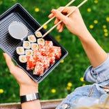 Hand holding sushi roll using chopsticks