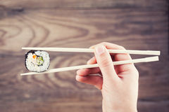 Hand holding sushi roll using chopsticks Royalty Free Stock Images