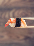 Hand holding sushi roll using chopsticks Royalty Free Stock Photo