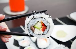 Hand holding sushi on sticks Royalty Free Stock Image