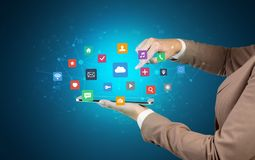 Hand holding tablet and application icons above. Female hand touching tablet with application icons above Royalty Free Stock Images