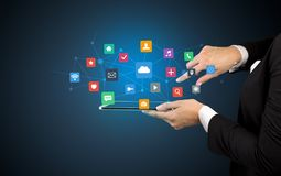 Hand holding tablet and application icons above. Female hand touching tablet with application icons above Stock Photos