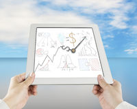 Hand holding tablet with business concept doodles and clock hand. S sky background Stock Photography