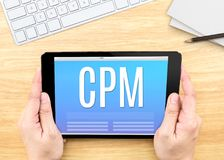Hand holding tablet with CPM Cost per mille  word on wood tabl. E ,Internet marketing concept Royalty Free Stock Images