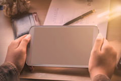 Hand of holding tablet on desk. Hand of woman holding a tablet and desktop devices Stock Photos