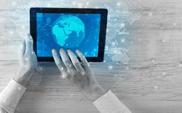 Hand holding tablet with global reports and stock market change concept Royalty Free Stock Photography