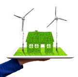 Hand holding a tablet with green house and wind turbines Stock Photos