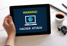 Hand holding tablet with hacker attack concept on screen Stock Photos