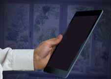 Hand holding tablet at home. Digital composite of Hand holding tablet at home Stock Image