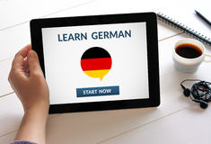 Hand holding tablet with learn german concept on screen Royalty Free Stock Photo