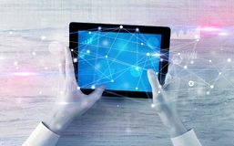 Hand holding tablet with linked graphs and charts concept. Hand using tablet with linking graphs charts report and informational flow concept stock photo