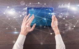 Hand holding tablet with linked graphs and charts concept. Hand using tablet with linking graphs charts report and informational flow concept royalty free stock photos