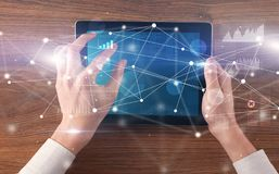 Hand holding tablet with linked graphs and charts concept. Hand using tablet with linking graphs charts report and informational flow conceptn royalty free stock photos
