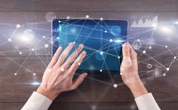 Hand holding tablet with linked graphs and charts concept. Hand using tablet with linking graphs charts report and informational flow conceptn stock photography
