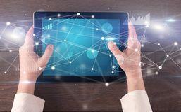Hand holding tablet with linked graphs and charts concept. Hand using tablet with linking graphs charts report and informational flow conceptn stock images
