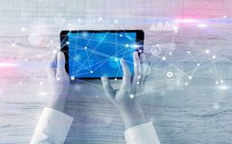 Hand holding tablet with linked graphs and charts concept. Hand using tablet with linking graphs charts  report and informational flow concept stock image