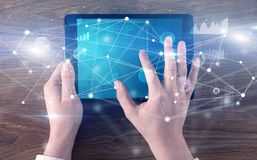 Hand holding tablet with linked graphs and charts concept. Hand using tablet with linking graphs charts  report and informational flow concept royalty free stock photo