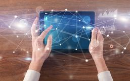 Hand holding tablet with linked graphs and charts concept. Hand using tablet with linking graphs charts  report and informational flow concept royalty free stock images