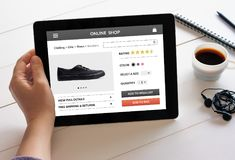 Hand holding tablet with online shop concept on screen. Hand holding digital tablet computer with online shop concept on screen. All screen content is designed Stock Image