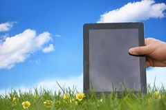 Hand holding tablet pc on meadow Stock Image