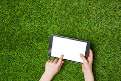 Hand holding tablet pc. over green grass Royalty Free Stock Images