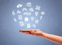 Hand holding tablet phone with drawn icons. An elegant caucasian white hand holding mobile phone with drawn social media icons in front of an empty clear blue Royalty Free Stock Photo