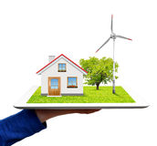 Hand holding a tablet with a wind turbine and house. Isolated on white background Stock Photography