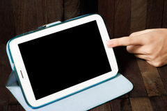 Hand holding a tablet on wooden background Stock Image