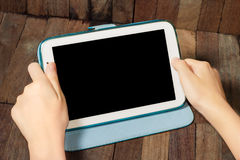 Hand holding a tablet on wooden background Stock Images